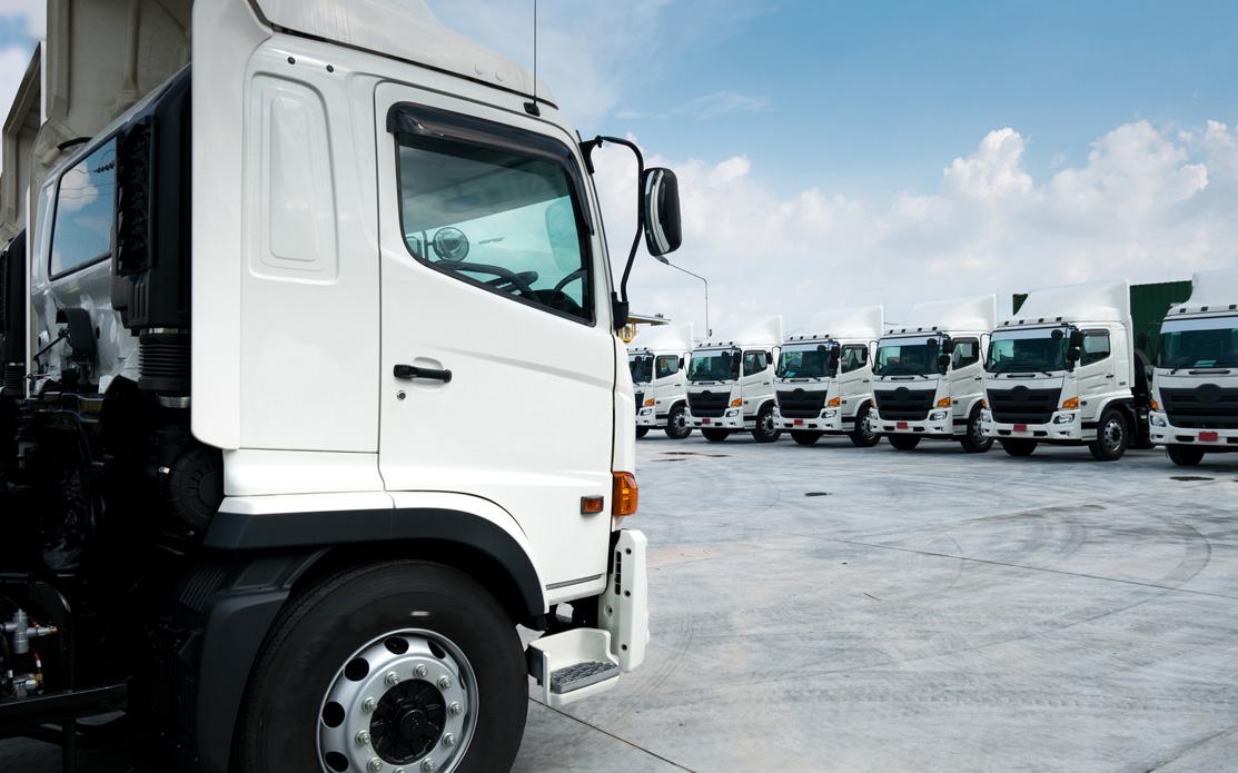 Fleet of white parked trucks : Invoice factoring & Asset Finance from Go-Factor
